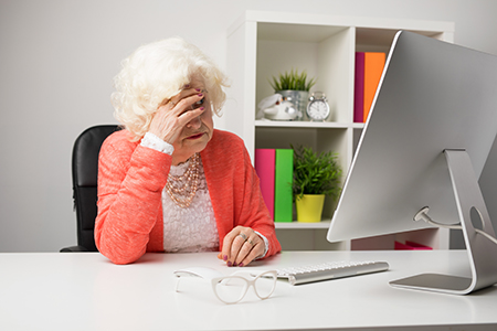 Frustrated senior in front of a computer